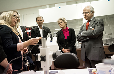 Vice-Chancellor Johan Schnürer, Professor Magnus Engwall, County Governor Maria Larsson and King Carl XVI Gustaf speaking with researchers Anna Kärrman and Anna Rotander.