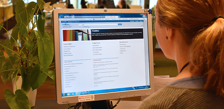 Person står vid datorskärm med databasen Pubmed