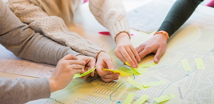 Hands are placing post-it notes on a map.