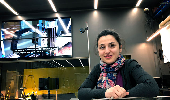 Marjan Alirezaie sitting at a desk in front of a large multi-screen