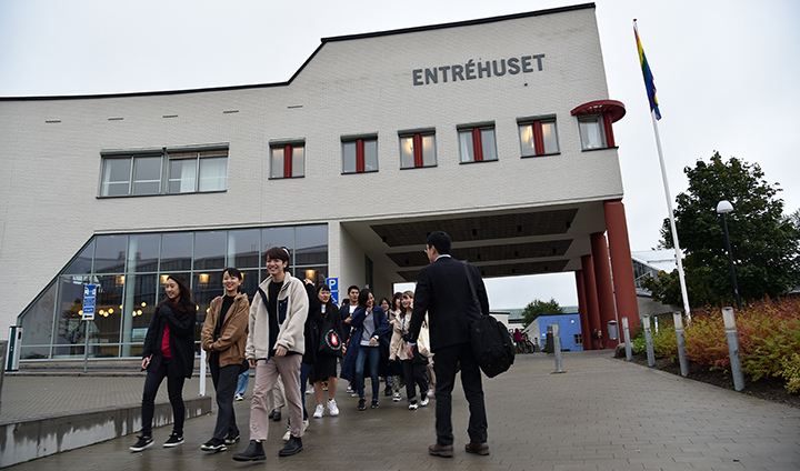 "Students and teaching staff from Yokohama walking in front of a white building that has the sign ""Entréhuset"". Students are laughing and enjoying themselves."