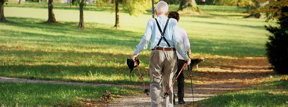 Two older people walking in the park.