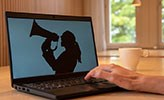 A computer. On the screen is a woman screaming in a megaphone.