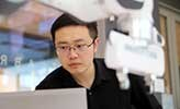 Researcher Da Sun, sitting in the robotics lab beside three robot arms.