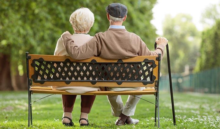 Äldre par på parkbänk
