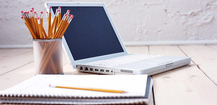Photo of a table with a laptop pencils and a note book.