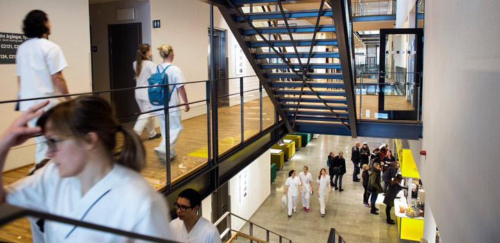 Female student wearing white lab clothes walking upstairs, with a group of students wearing white lab clothes in the lobby below.