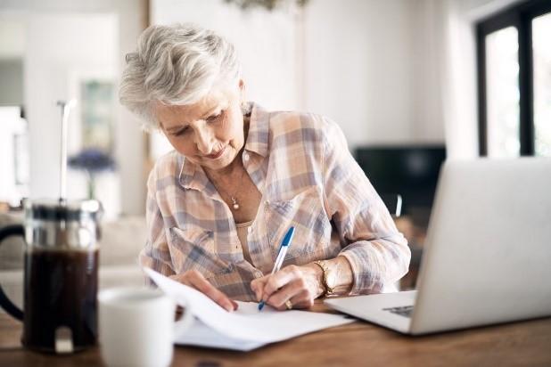 En äldre kvinna sitter vid ett bord och skriver