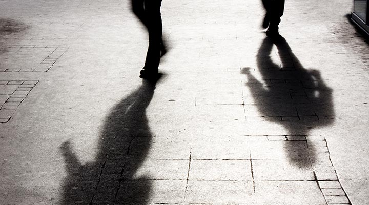 Two shadows from people walking on a sidewalk.