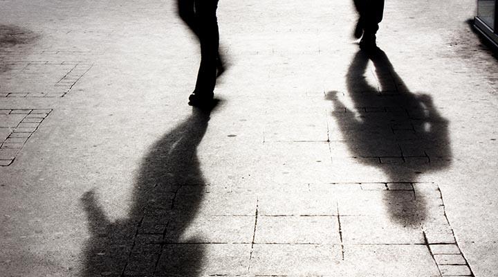 Två skuggor från personer som går från en trottoar.