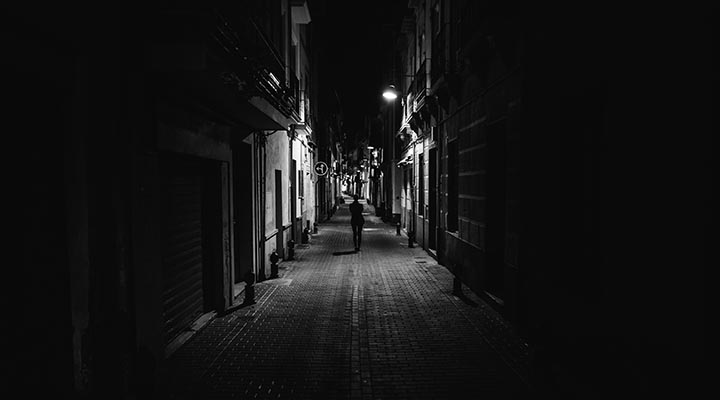 En kvinna går ensam i en mörk gränd.