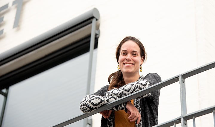 Alina Koch, smiling and standing on a balcony.